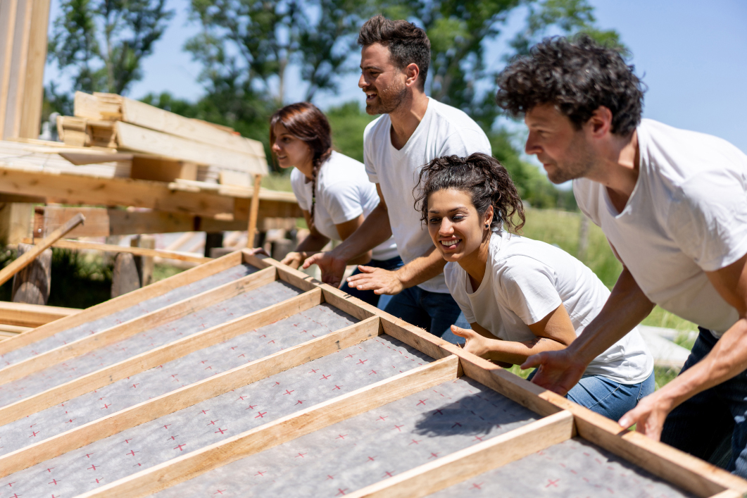Men and women helping to build a house